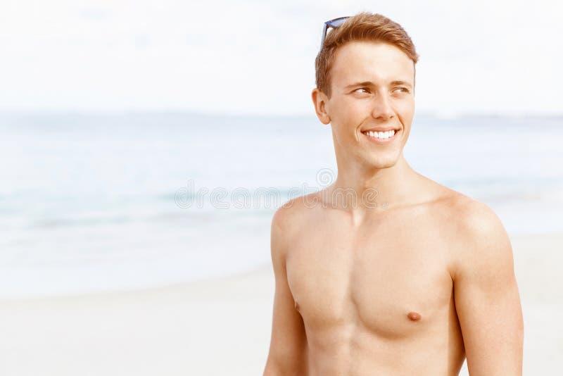摆在海滩的英俊的人 免版税库存照片