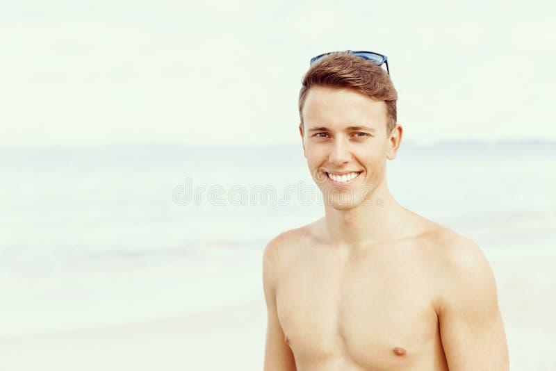 摆在海滩的英俊的人 免版税库存图片