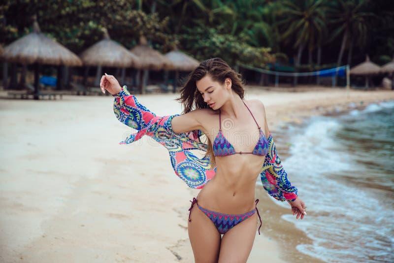 摆在海滩的蓝色比基尼泳装的美丽的年轻深色的妇女 与完善的身体的性感的式样画象 概念  免版税图库摄影