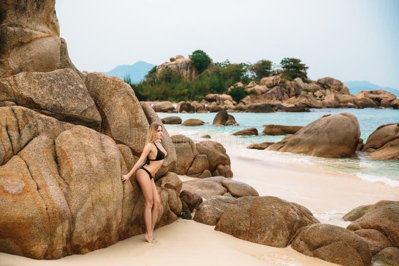 摆在海滩的黑比基尼泳装的美丽的年轻白肤金发的妇女 与完善的身体的性感的式样画象 概念  免版税库存照片