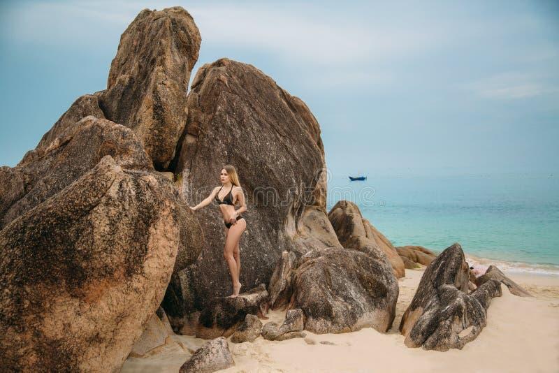 摆在海滩的黑比基尼泳装的美丽的年轻白肤金发的妇女 与完善的身体的性感的式样画象 概念  库存图片