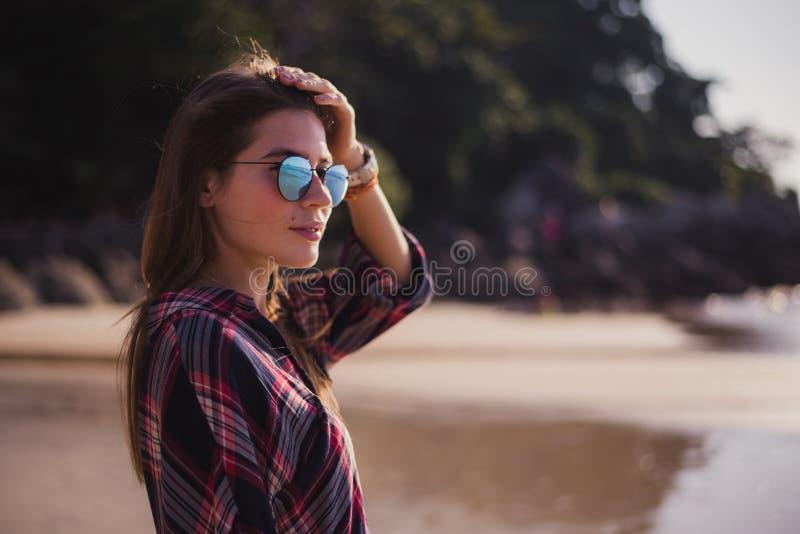 摆在海滩的年轻美丽的时髦的女孩在一个大风天 库存照片
