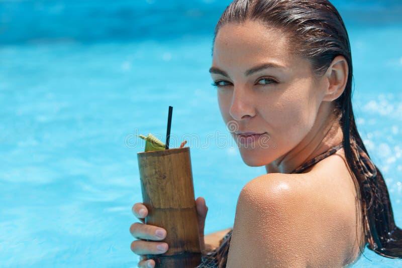 摆在游泳场中部的神奇有吸引力的模型接近的画象,拿着在木容器的鸡尾酒,看 库存照片