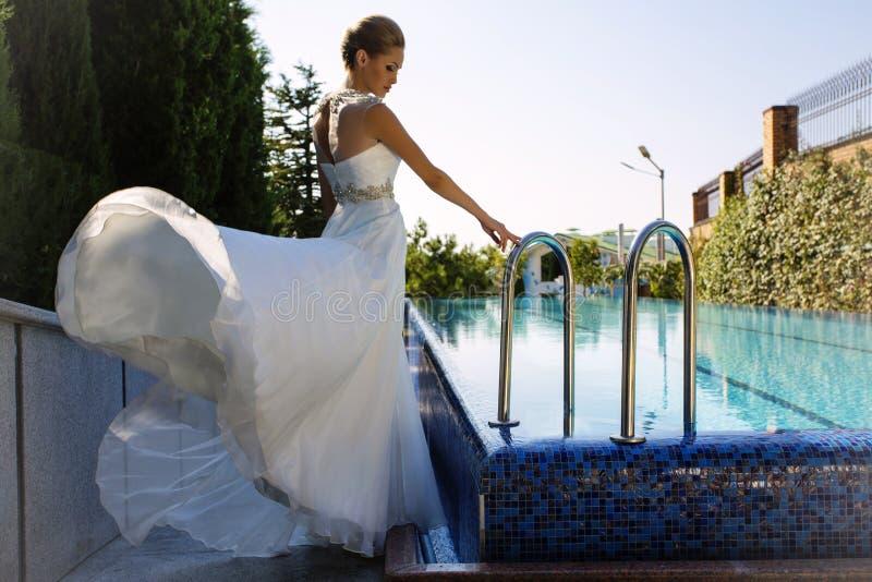 摆在游泳池旁边的典雅的婚礼礼服的美丽的新娘 库存图片