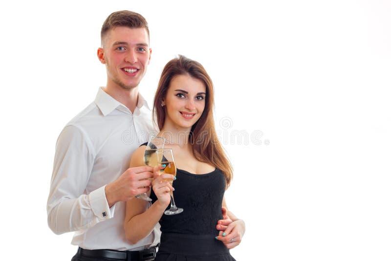 摆在演播室和拿着的微笑的夫妇酒杯 免版税库存照片