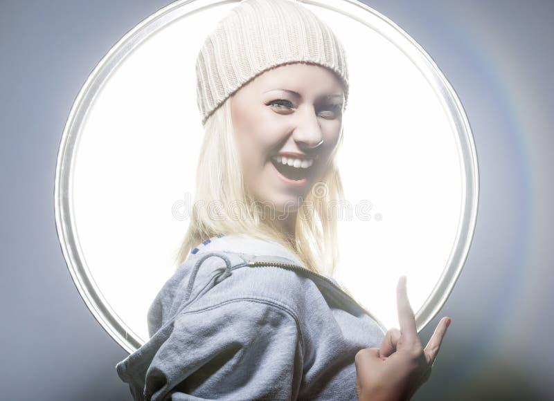 摆在演播室环境里的年轻和性感的愉快的白肤金发的妇女  免版税库存图片