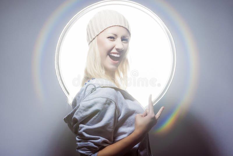 摆在演播室环境里的年轻和性感的愉快的白肤金发的妇女  免版税库存照片