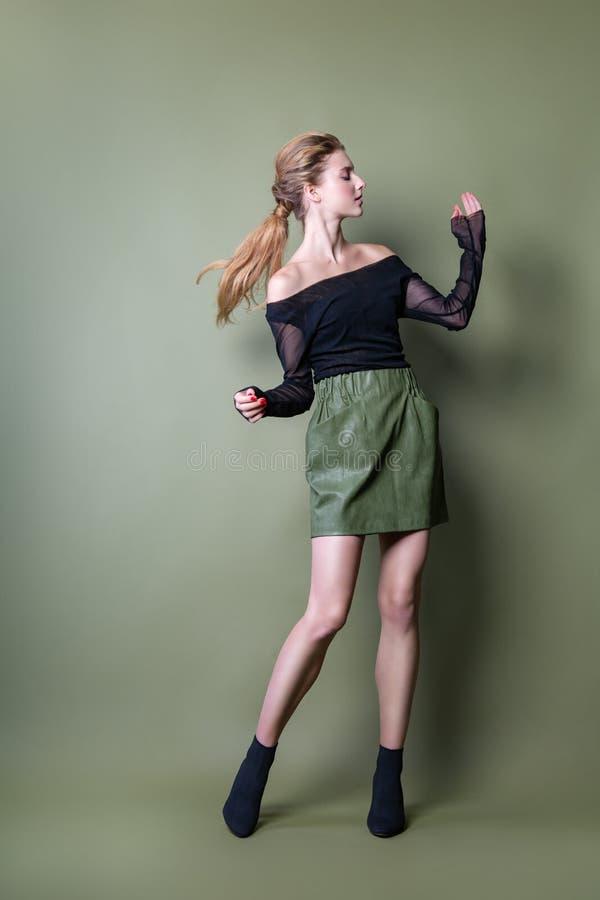摆在演播室的一条黑夹克和绿色裙子的年轻美女 在时髦的便服的有吸引力的女性模型 免版税库存图片