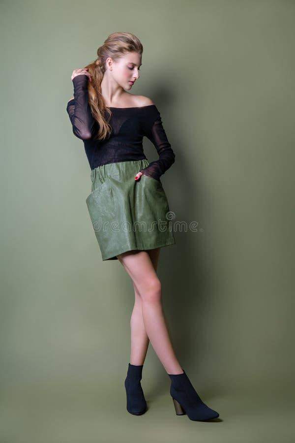 摆在演播室的一条黑夹克和绿色裙子的年轻美女 在时髦的便服的有吸引力的女性模型 库存图片
