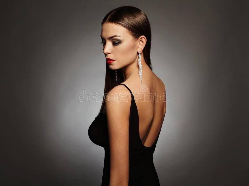 摆在演播室的一件黑性感的礼服的美丽的少妇,豪华 秀丽浅黑肤色的男人女孩 免版税库存图片