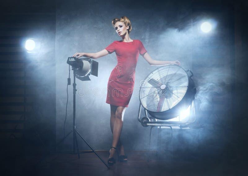 摆在演播室的一件红色礼服的一名妇女 免版税库存照片