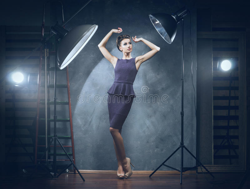 摆在演播室的一件蓝色礼服的一名妇女 免版税库存图片