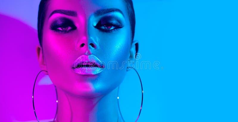 摆在演播室的五颜六色的明亮的霓虹灯的时装模特儿深色的妇女 美丽的性感的女孩,时髦发光的构成 免版税库存图片