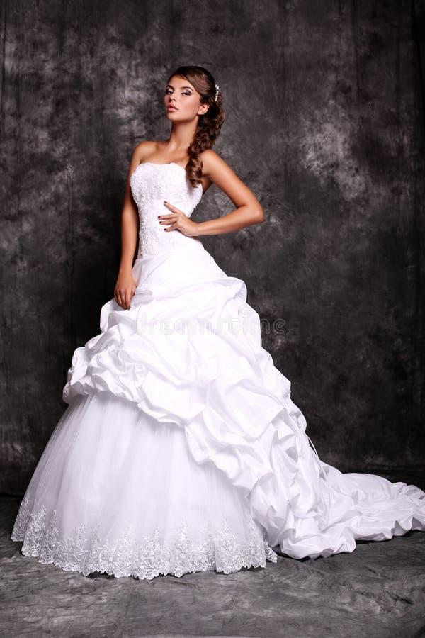 摆在演播室的婚礼礼服的美丽的年轻新娘 免版税图库摄影