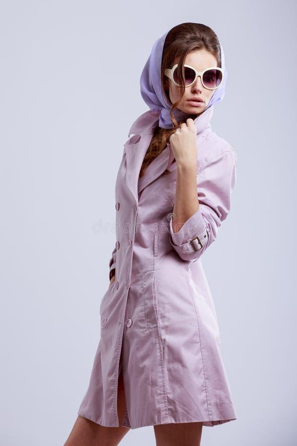 摆在演播室的年轻时尚妇女戴桃红色外套和白色太阳镜 免版税库存照片