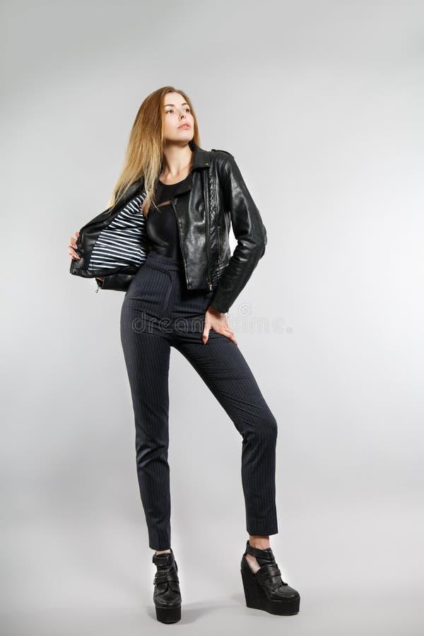 摆在演播室的年轻时髦的女孩 黑皮包骨头的裤子,黑皮夹克 库存照片