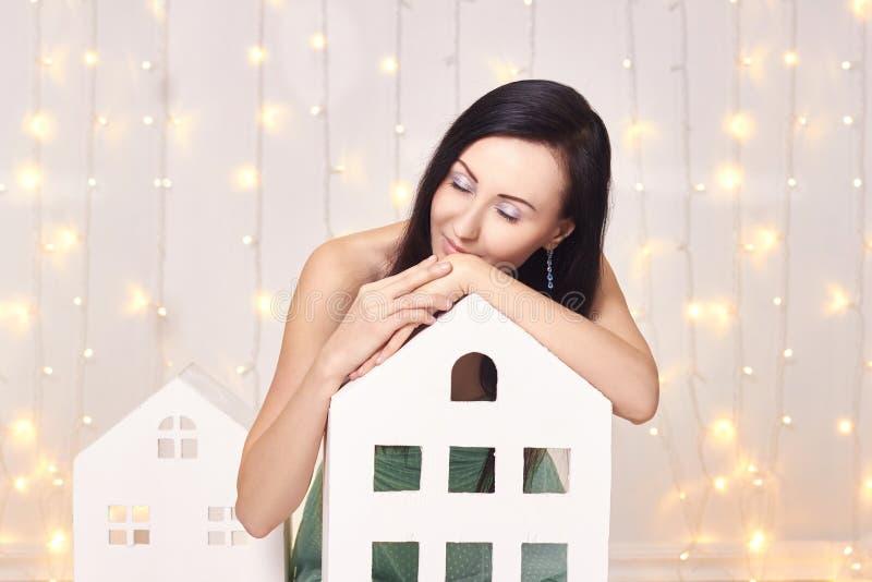 摆在演播室的短的绿色礼服的浅黑肤色的男人在儿童` s玩具房子附近 背景的美丽的可爱的女孩 免版税图库摄影