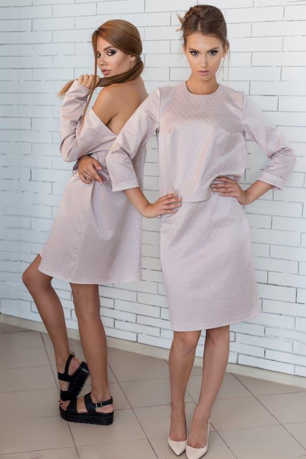 摆在演播室的米黄时兴的礼服的两个美丽的性感的时髦的愉快的女孩 免版税库存照片
