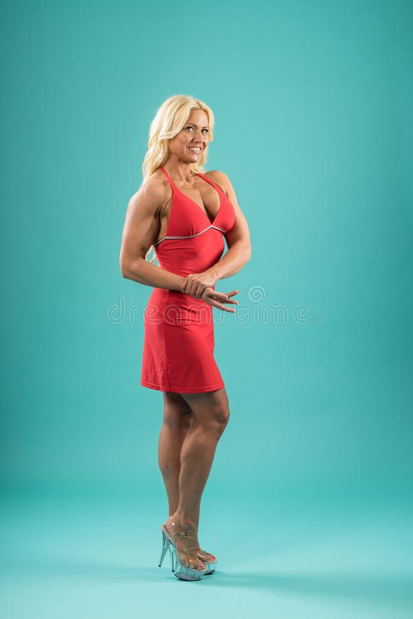 摆在演播室的红色礼服的运动妇女 有显示她的肌肉的长的金发的可爱的健身夫人 免版税库存图片