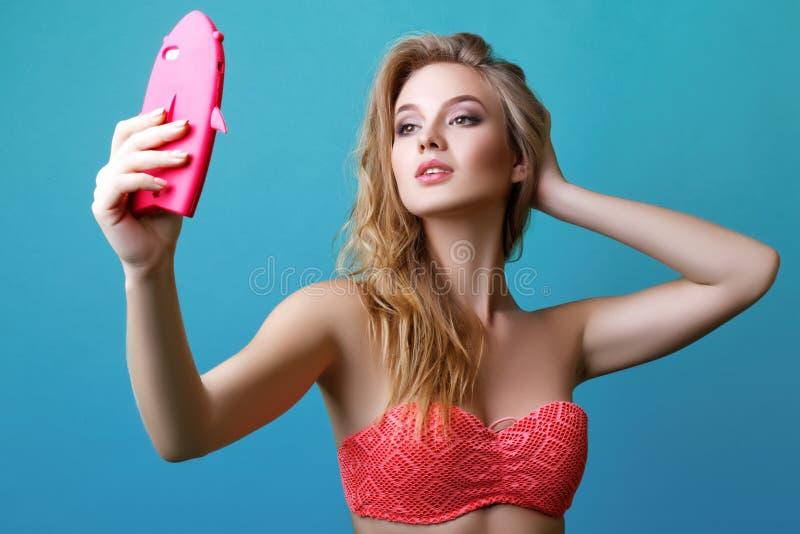 摆在演播室的美丽的年轻白肤金发的妇女泳装的和有电话的 库存照片