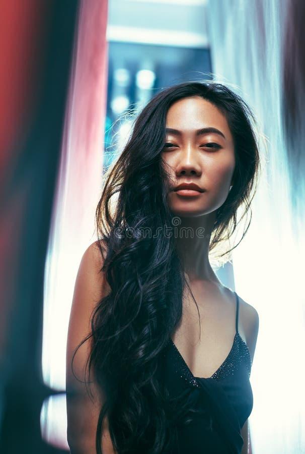 摆在演播室的黑礼服的美丽的亚裔妇女 免版税图库摄影