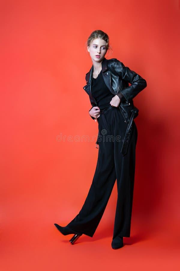 摆在演播室的黑色衣服的年轻美女 在时髦的便服的有吸引力的女性模型 库存照片