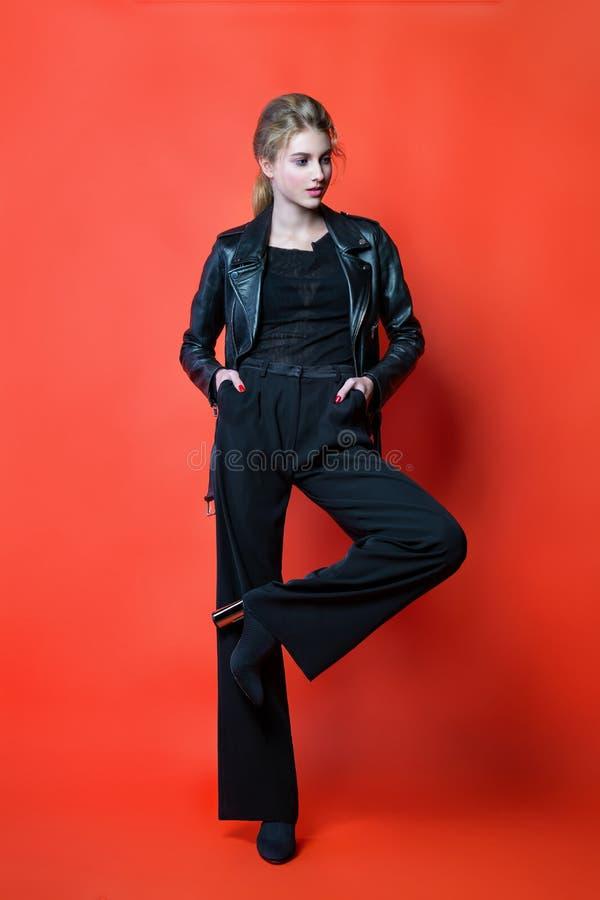 摆在演播室的黑色衣服的年轻美女 在时髦的便服的有吸引力的女性模型 免版税库存照片