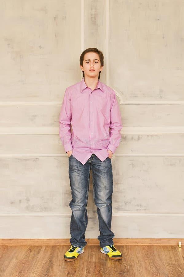 摆在演播室的年轻俏丽的男孩作为时装模特儿 免版税库存照片