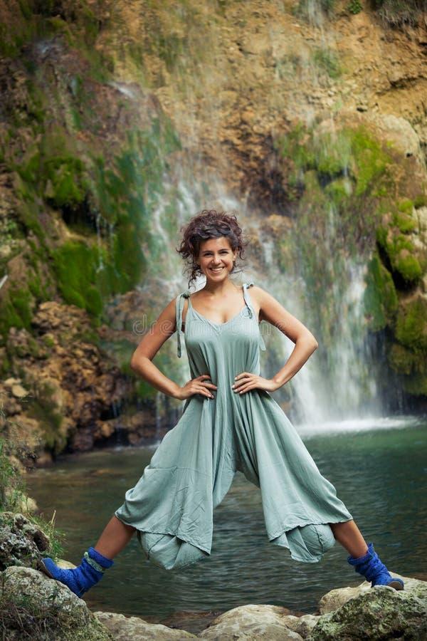 摆在瀑布夏天前面的微笑的少妇 库存图片