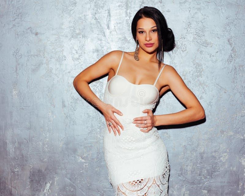 摆在灰色墙壁背景的一件时髦白色礼服的美丽的性感的年轻深色的妇女在演播室 库存图片