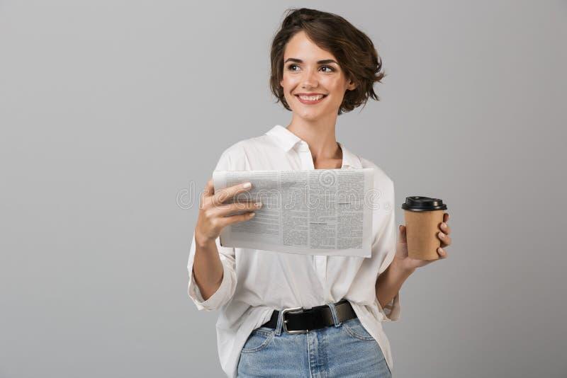 摆在灰色墙壁背景阅读报纸饮用的咖啡的情感年轻女商人 免版税库存图片