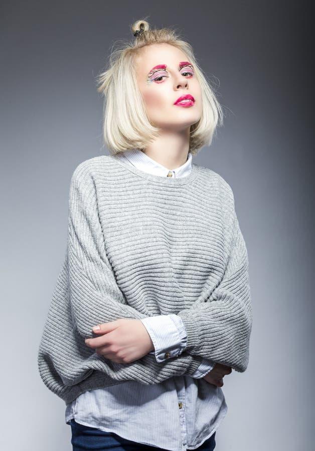 摆在灰色毛线衣的年轻白种人白肤金发的妇女自然秀丽画象  免版税库存图片