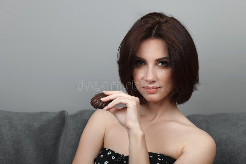 摆在灰色沙发wa的秀丽画象运动的成人可爱的新看起来的深色的妇女巧克力曲奇饼华美的构成突然移动发型 免版税库存照片
