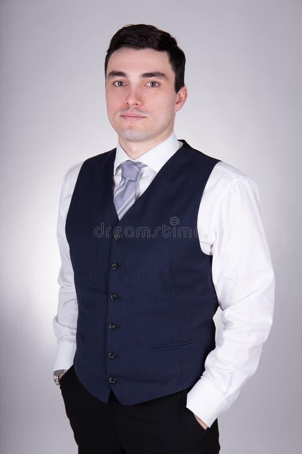 摆在灰色的年轻英俊的商人 库存照片