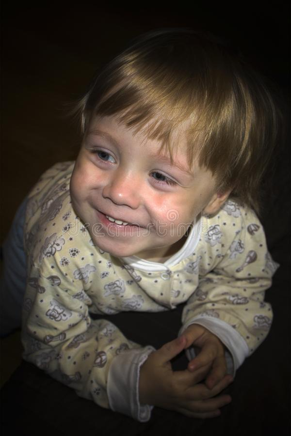 摆在照相机前面的小逗人喜爱的微笑的白肤金发的男孩 免版税图库摄影