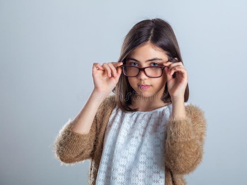 摆在照相机前面的玻璃的可爱和美丽的少年女孩在演播室 库存图片