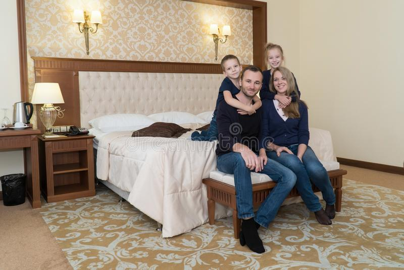 摆在照相机的一个愉快的家庭在旅馆客房坐床 库存图片