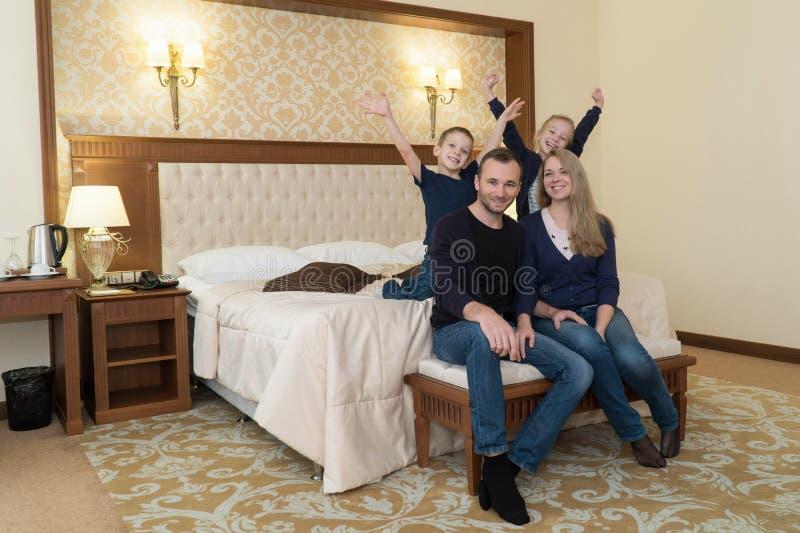 摆在照相机的一个愉快的家庭在旅馆客房坐床 免版税库存图片