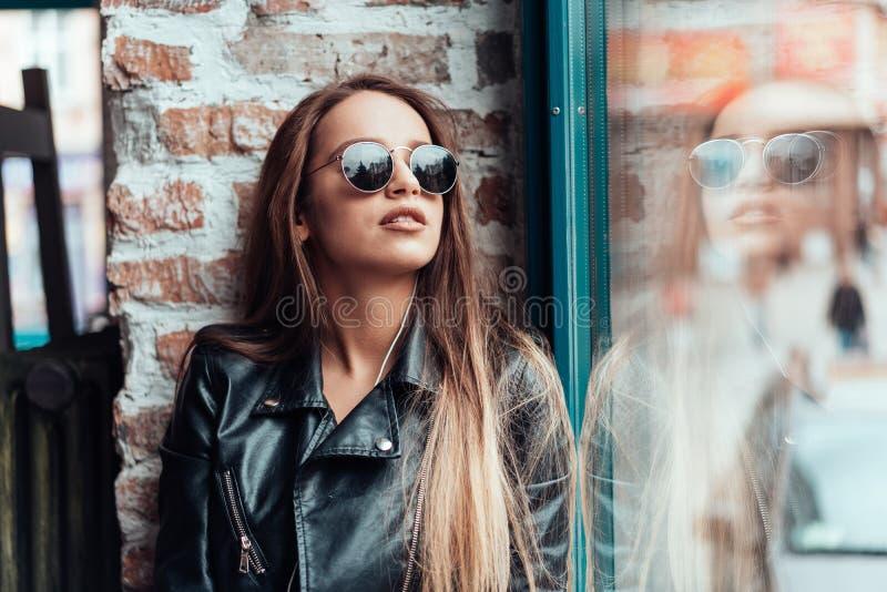 摆在照相机的太阳镜的美丽的女孩 免版税库存照片