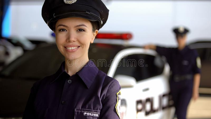 摆在照相机的微笑的亚裔女警反对伙伴在巡逻车,义务附近 免版税库存照片