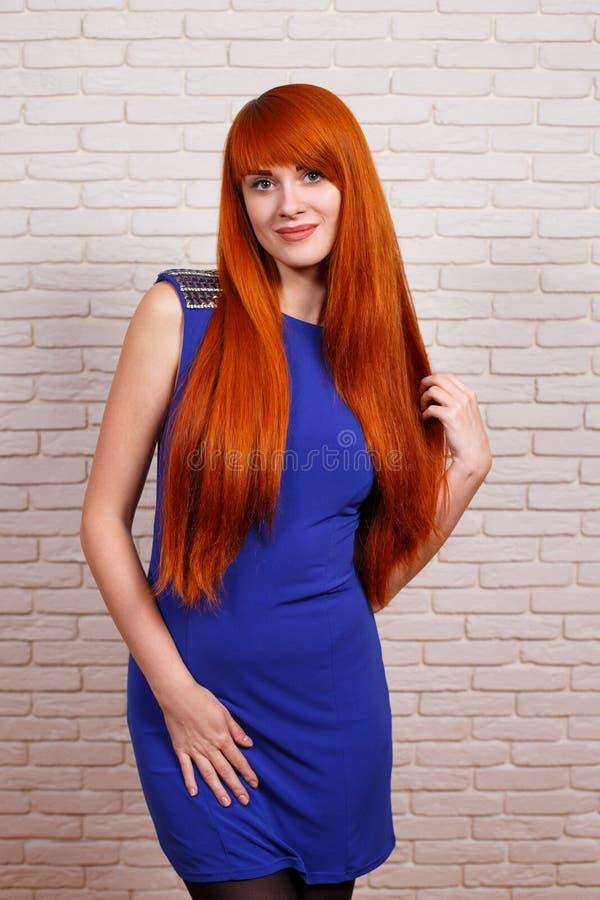 摆在照相机的晚礼服的年轻美丽的红头发人妇女 免版税图库摄影