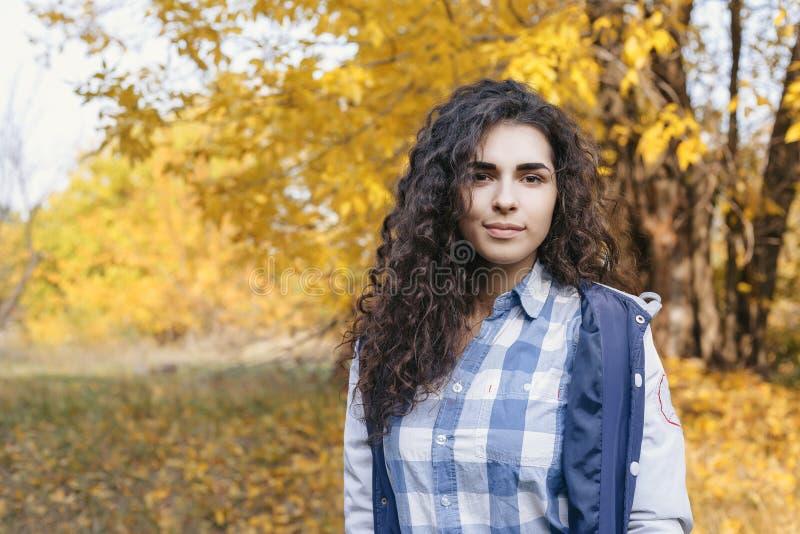 摆在照相机的混合的族种妇女在秋天公园 免版税库存图片