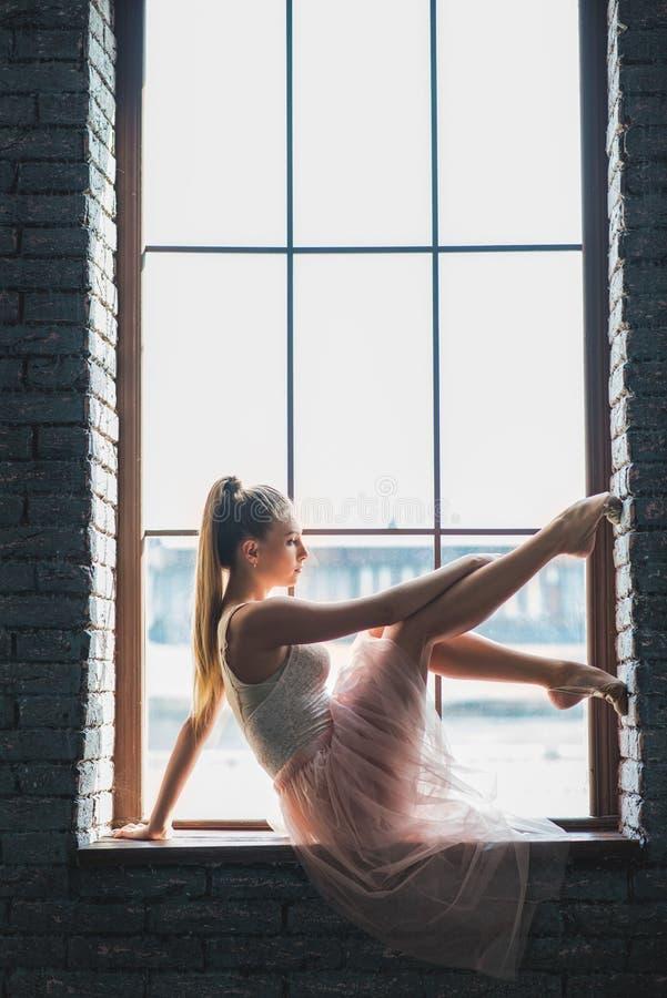 摆在照相机的年轻舞蹈家在窗口附近 图库摄影