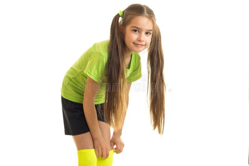 摆在照相机的绿色足球制服的俏丽的女孩 库存图片