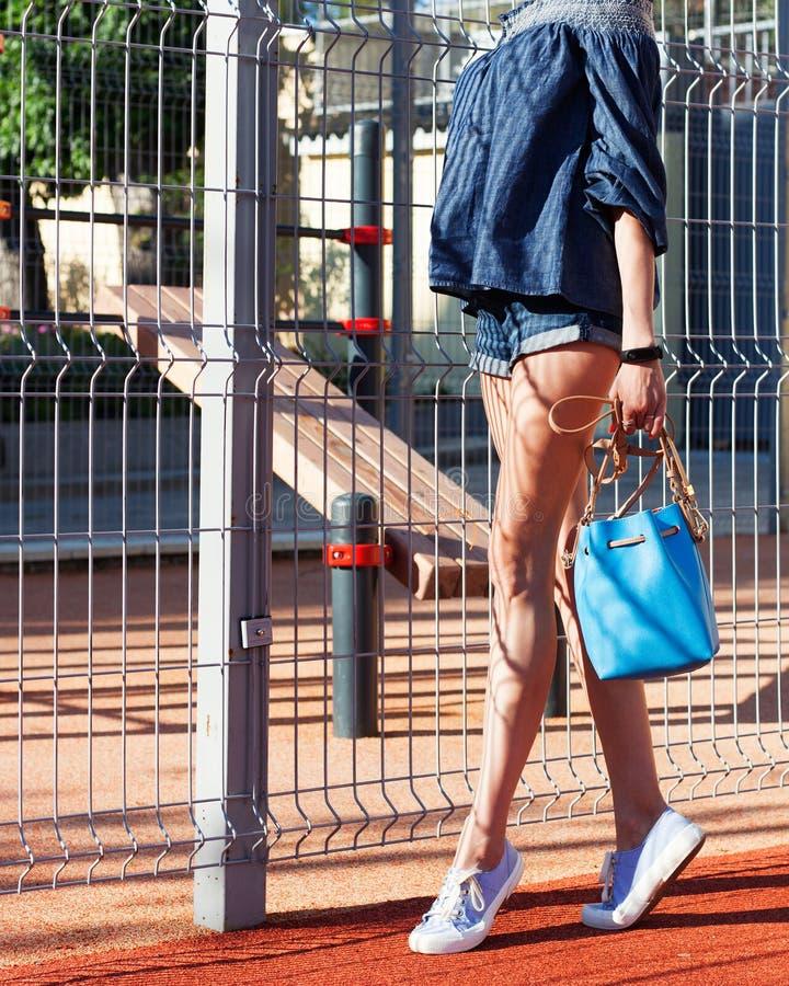 摆在牛仔裤成套装备,运动鞋的一个少妇和与在的一个superfashionable蓝色手袋体育在一个夏日停放 免版税图库摄影