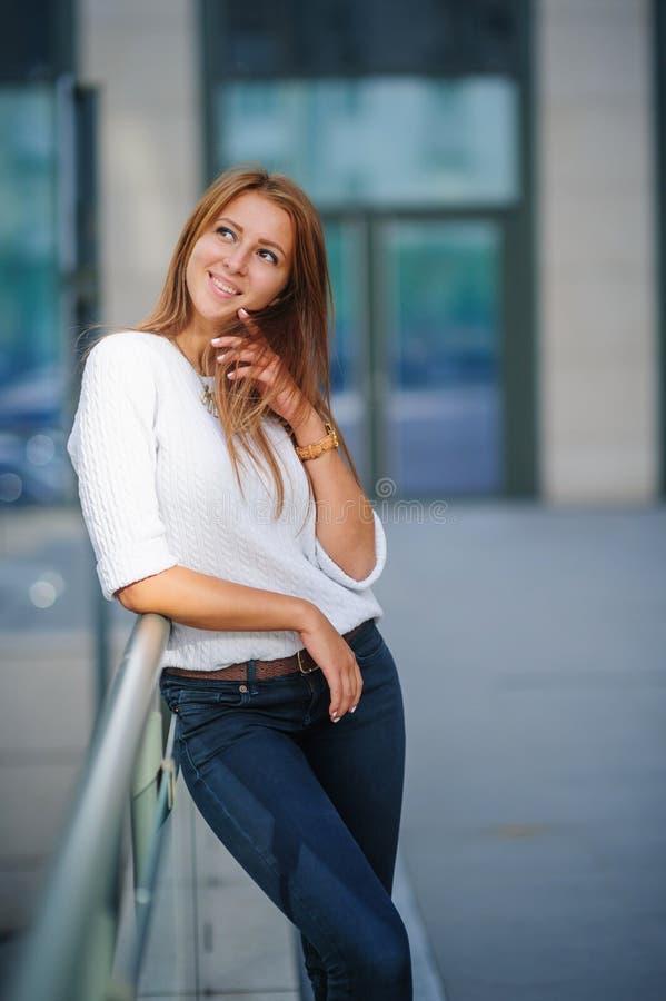 摆在现代城市的年轻微笑的妇女 免版税库存照片