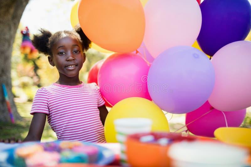 摆在生日聚会的气球旁边的逗人喜爱的女孩 免版税库存图片