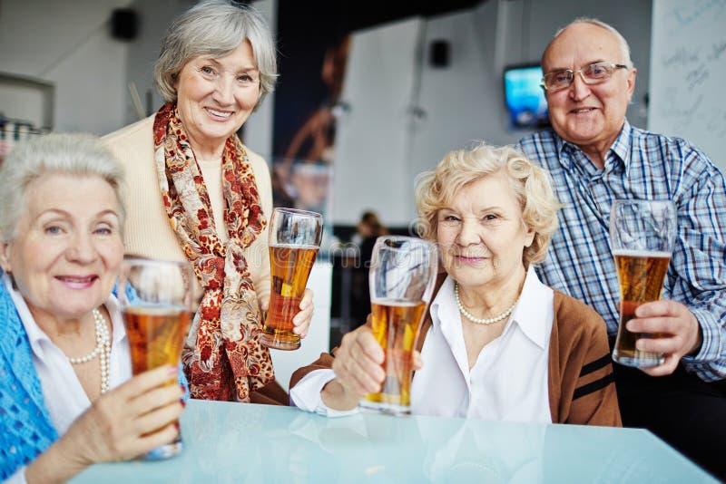 摆在用啤酒的资深人民 库存图片