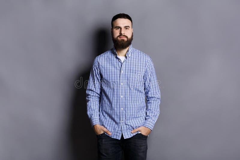 摆在用在口袋的手的英俊的有胡子的人 库存图片