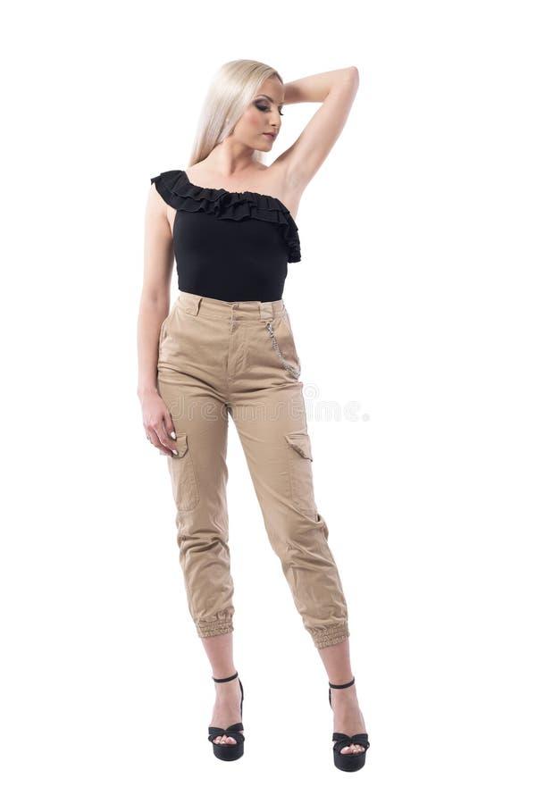 摆在用在看的头后的手的时髦迷人的白肤金发的妇女下来 免版税库存图片